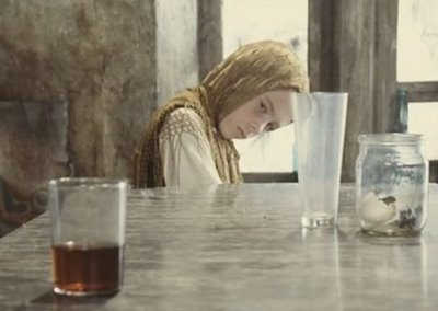 A still from Tarkovksy's Stalker showing a young girl moving a bottle with her mind